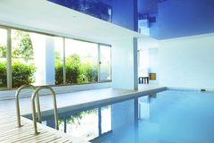 Swimming pool area of new luxury residential complex with tiles, chrome stairs handles and drains. Sunny beautiful day. royalty free stock photos