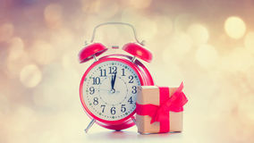 Big red alarm clock and beautiful gift on the fairy lights bokeh Stock Images