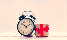 Big red alarm clock. dotted ribbon and beautiful gift on the won Stock Photo