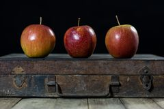 Big red apples in a dark wooden box. Wooden crate and apples on. A wooden table in the kitchen. Black background Royalty Free Stock Photography
