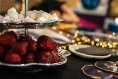 Big red berries of strawberry and white marshmallow pieces in silver vintage 2-levels serving plate on the table with blurry stock photo