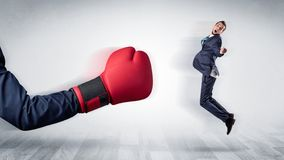 Red boxing glove knocks out little businessman royalty free stock image