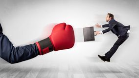 Red boxing glove knocks out little businessman stock photography