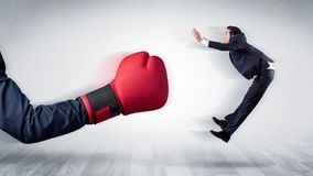 Red boxing glove knocks out little businessman royalty free stock photo