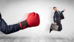 Red boxing glove knocks out little businessman. Big red boxing glove knocks out little businessman conceptn Royalty Free Stock Photo