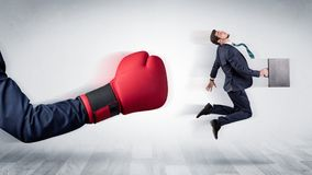Red boxing glove knocks out little businessman. Big red boxing glove knocks out little businessman conceptn Stock Photo