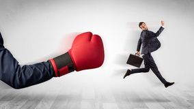 Red boxing glove knocks out little businessman. Big red boxing glove knocks out little businessman conceptn Stock Image