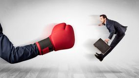 Red boxing glove knocks out little businessman. Big red boxing glove knocks out little businessman conceptn Stock Photography