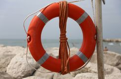 Big red buoy on the rocks to help swimmers Stock Image