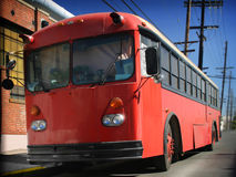 Big Red Bus. Big red old bus on city street with telephone poles and brick wall Stock Images
