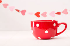 Big red coffee mug and hearts garland Stock Images