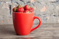 Big red cup filled with succulent juicy fresh ripe red strawberries on an old wooden textured table top with brick background Stock Image
