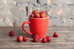 Big red cup filled with succulent juicy fresh ripe red strawberries on an old wooden textured table top with brick background Stock Photography