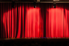 Big red curtain. A closed red stage curtain in a small theater royalty free stock photos