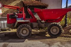 A big red dump truck in front of a building under construction. stock image
