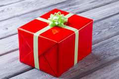 Big red gift box on a wooden background. Stock Photos