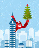 Big Red Gorilla dressed as Santa Claus climbs the building with Royalty Free Stock Images
