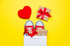 Big red gumshoes, beautiful gifts and alarm clock in cool shoppi Royalty Free Stock Images