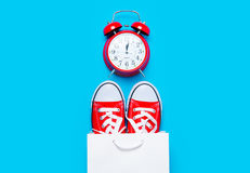 Big red gumshoes in cool shopping bag and alarm clock on the won Stock Image