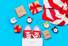 Big red gumshoes in cool shopping bag, alarm clocks and striped Royalty Free Stock Images