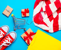 Big red gumshoes in cool shopping bag, shopping cart and beautif Royalty Free Stock Image