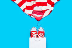 Big red gumshoes in cool shopping bag and stried jacket on hange Stock Image