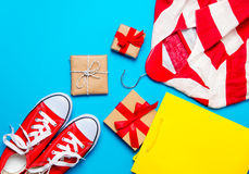 Big red gumshoes, cool shopping bag, striped jacket on hanger an Royalty Free Stock Image