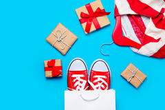 Big red gumshoes in cool shopping bag, striped jacket on hanger Stock Photography