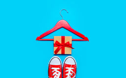 Big red gumshoes, hanger and beautiful gift on the wonderful blu Stock Photo