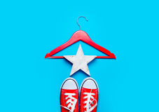 Big red gumshoes, hanger and beautiful star shaped toy on the wo Royalty Free Stock Photography