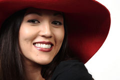 Big Red Hat. A portrait of a pretty young woman on a white background in a red hat with a big smile on her face Stock Photo