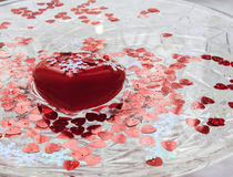 Big red heart floats in water. Valentine`s day. A red heart. White snowflakes. A dish of water. Heart floats in water Stock Photo