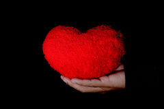 Big red heart on hand. And black background Royalty Free Stock Image