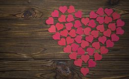 Big red heart laid out from little hearts. A background of a textured wood table. Holiday, St. Valentine`s Day, lovers` day, anniversary Stock Photo
