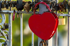 Big red heart shaped lock hanging on a bridge.  Royalty Free Stock Photos