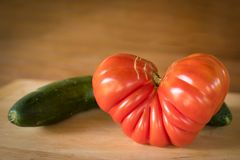 Big red heart-shaped tomato and cucumber on a wooden plate. Closeup of a big red heart-shaped tomato and cucumber on a wooden plate royalty free stock photos