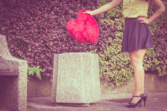 Big red heart on trash can. Love and feelings. Part body woman with big red heart on trash can. Hurt and depressed person throwing out sign of loving Royalty Free Stock Photos