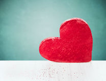 Big red heart on white wooden table over  blue background Royalty Free Stock Photography