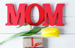 Big red letters Mom lies on the table with gift card and yellow tulips. Flowers for gift. Mother`s day concept. Big red letters Mom lies on the table and yellow royalty free stock photography