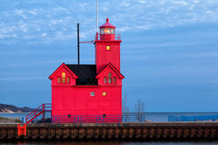 Big Red Lighthouse in Holland Michigan. Holland Harbor Light, locally known as Big Red is starkley vivid in this early eveing scene. Lights glow golden from the Stock Photo