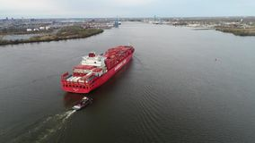 Big red loaded freight cargo container ship arriving at modern urban industrial river ocean port in 4k aerial drone view. Big red loaded freight cargo container stock video
