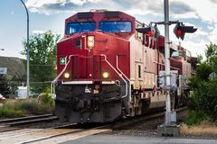 Big Red Locomotive Passing a Railroad Crossing Royalty Free Stock Photo