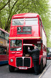 Big red London bus open hood. Driver looking into motor of a London bus on treelined street Royalty Free Stock Photography