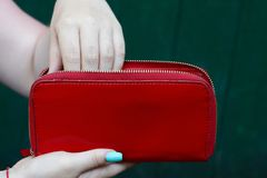 Big red purse in the hands of a girl. Hand of a girl in a big red purse on a green background Stock Images