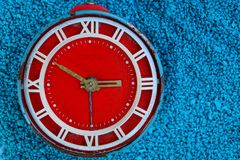 Big red old alarm clock on blue background royalty free stock photo