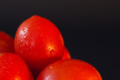 Big red ripe tomatoes with water droplets on a black background Royalty Free Stock Image