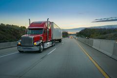 Big red semi truck on road. Red semi tractor trailer on the highway at sunset Royalty Free Stock Images