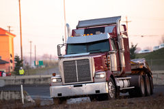 Big red semi truck turn on the highway ramp Stock Photos