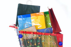 Big red shopping cart full of shopping bags stock photography