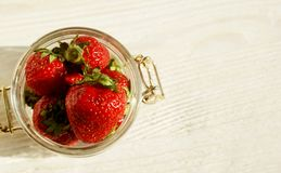 Big red sweet strawberry in a glass jar on a wooden table. Sweet red large berries in a glass jar on a wooden table royalty free stock image